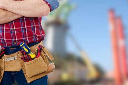 Erbauer mit dem Gürtel von Werkzeugen auf Hintergrund zu im Freien