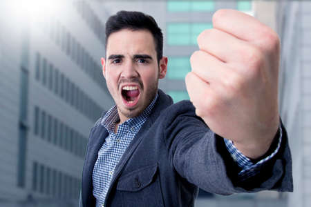 young man yelling with his fist in the foreground