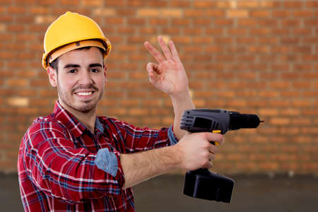 builder with the drill and the sign of approval, okay Reklamní fotografie