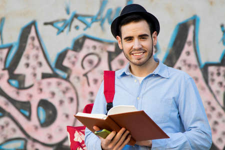 outerwear: portrait of young man with hat to the urban fashion with the book