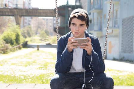 niños platicando: child with the cellphone in park swings Foto de archivo