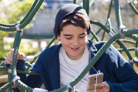 niños jugando videojuegos: niño con el teléfono móvil en el patio al aire libre