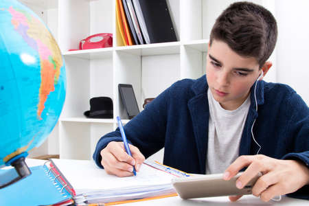 concentrate: child writing and studying at the school desk