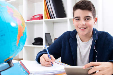 gifted: child writing and studying at the school desk