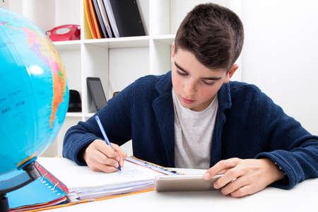 Niño escribiendo y estudiando en el escritorio de la escuela Foto de archivo