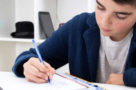 child writing and studying at the school desk