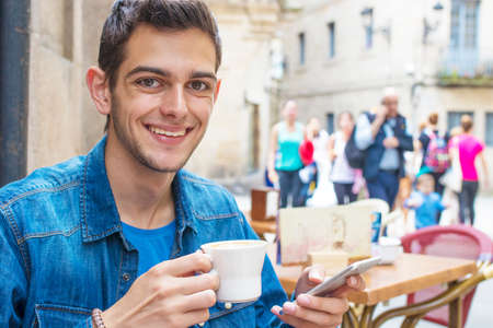 young man drinking coffee on the terrace Stock Photo