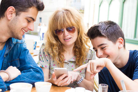 Young family drinking coffee and playing mobile phone