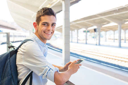 young man with the backpack at the train station, travelers