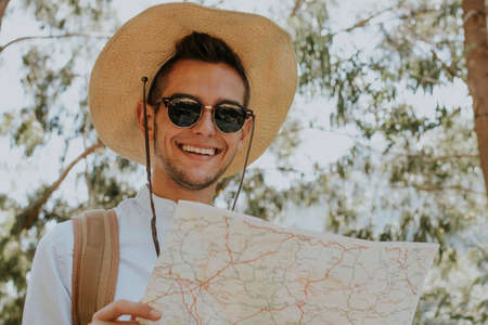 young man with the journey of adventure and expedition map