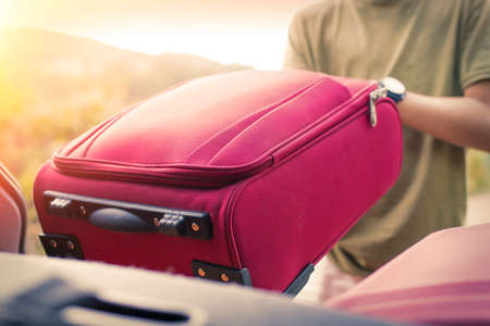 Putting the suitcase in the car boot, luggage and travel concept
