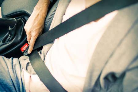 A man's hand fastening the car seatbelt Foto de archivo