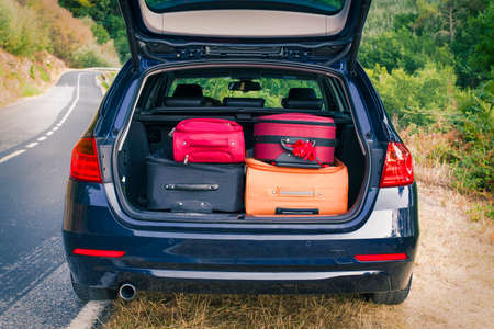 car with trunk loaded with suitcases and luggage Stock Photo