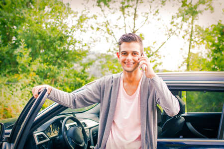 young man with mobile phone in the car Foto de archivo