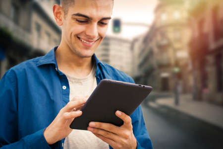 young smiling with the digital tablet in the city