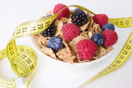 cup with cereals and fruits of the forest with tape measure, concept of diet and health