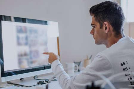 自宅やオフィスでコンピュータを扱う若者