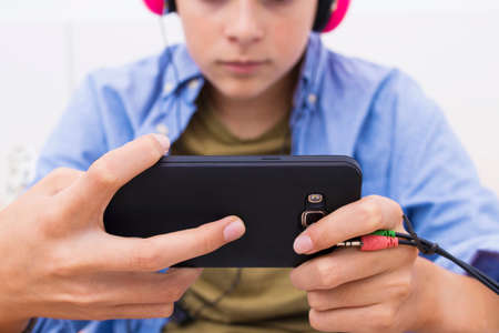 young teenager with a mobile phone listening to music or playing