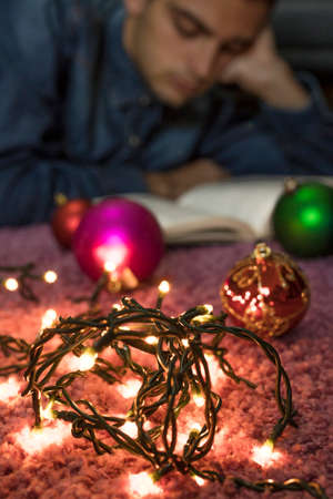 young at home reading with christmas decorations and lights Stock Photo