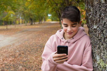 teenager talking on mobile phone outdoors in autumn Stock Photo