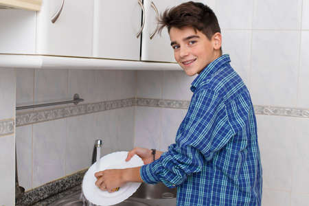 boy, young, teenager or preteen scrubbing the dishes