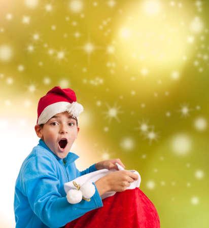 bambino con espressione sorpresa con sacco regalo di Babbo Natale a Natale