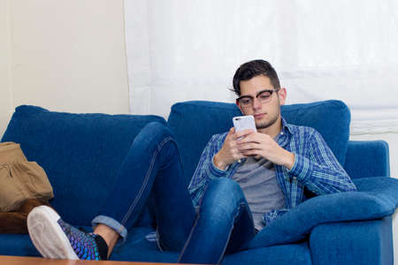young man with mobile phone on the sofa in the apartment