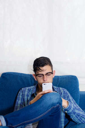young casual in the home sofa with mobile phone Stock Photo