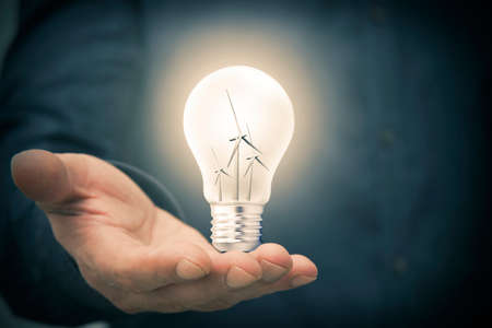 hand with light bulb and windmills, concept of renewable energies Stockfoto