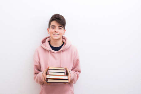 teenage student with books on the white wall 版權商用圖片