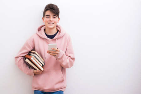 teenage student with books on the white wall Stock Photo