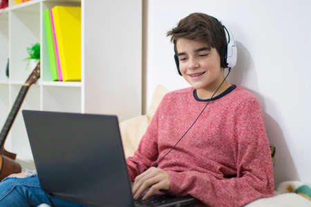 young teenager with laptop at home