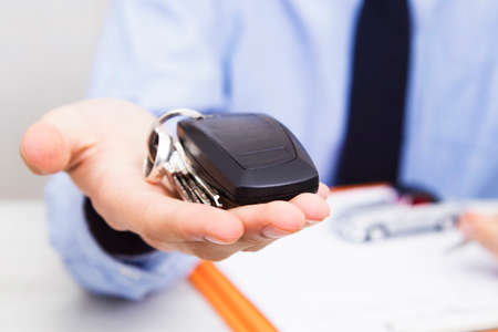 business man hand with keys and car control