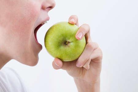 Mond bijten de appel met witte ruimte
