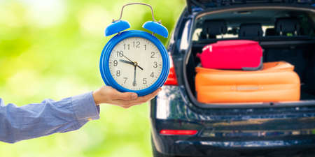 hand-clock and car with trunk and suitcases, holidays and trips