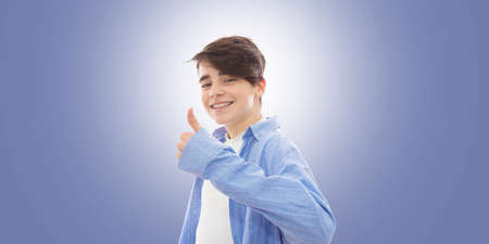 young man smiling with braces and thumbs up approval sign