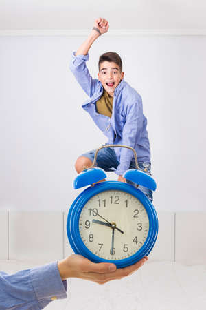 hand with watch and young jumping on the bed happy