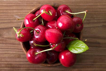 red cherries on rustic wood
