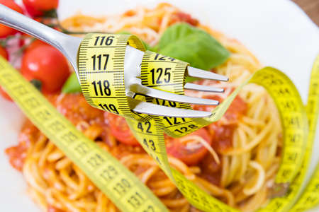 fork with tape measure and food background, diet concept