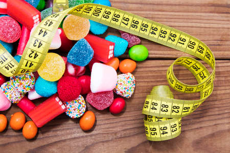 candy and candies with tape measure, foods forbidden to lose weight