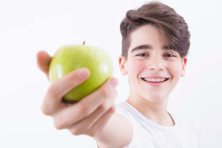 teenager smiling with braces and fresh green apple, dentures and oral health
