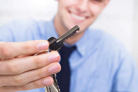 business man with key in hand, real estate and buy house