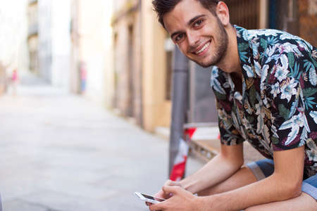 portrait of smiling young man with mobile phone on the street