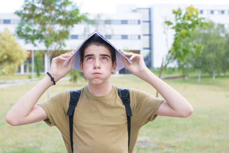 stressed or overwhelmed student with notebook on head