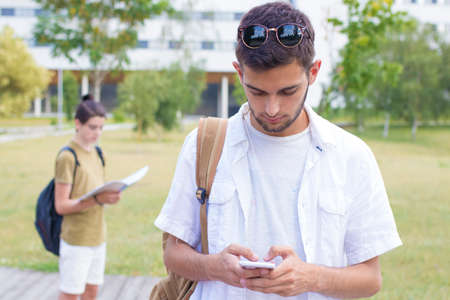 student with mobile phone on the university campus
