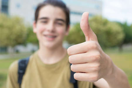 young teenage student with thumbs up in sign of success and approval