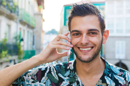 portrait of young man smiling talking on mobile phone in the city