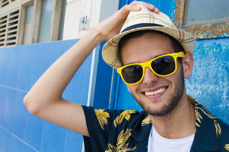 portrait of smiling young man with sunglasses and hat Stock Photo