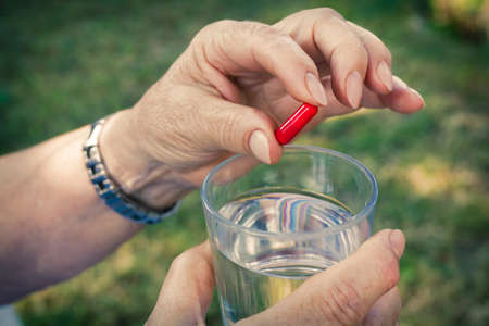 older woman hand with pills and a glass of water