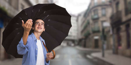 young with umbrella in town watching if it rains